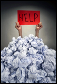 A pair of hands extending from a pile of rags holding a handwritten sign saying HELP