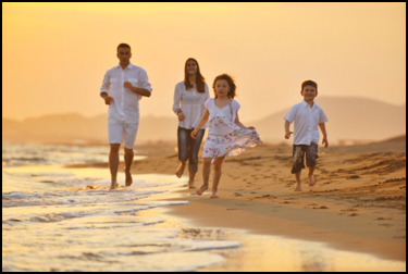 A family of four jogging down the beach
