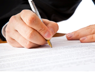 A suited arm and hand writing on a paper with a stylus